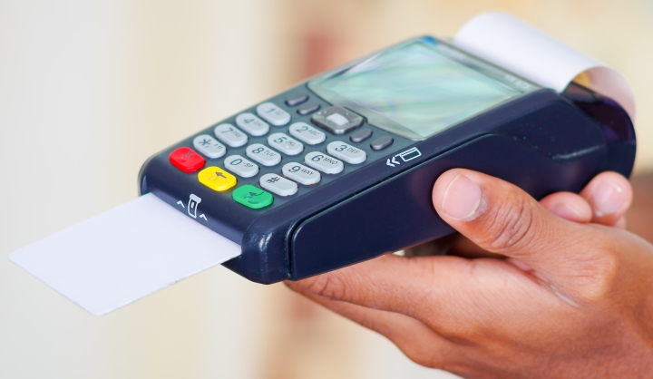 Closeup hands holding up credit card payment terminal in front of camera, profile angle